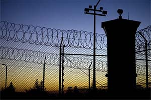 night sky, surveillance tower and fence with razor wire